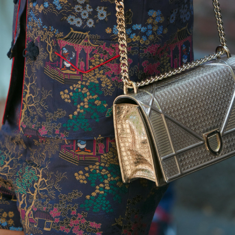 Image of Woman wearing designer clothes with a gold dior bag.